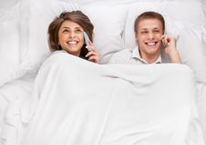 Couple lying and chatting in bed Royalty Free Stock Photos