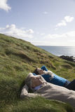 Couple Lying On Coastal Landscape Royalty Free Stock Image