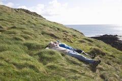 Couple Lying On Coastal Landscape Royalty Free Stock Images
