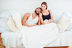 Couple lying on the couch and drinking coffee Stock Image