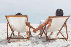Couple lying on deck chairs Royalty Free Stock Photography