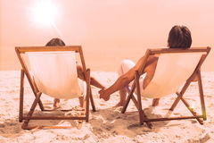 Couple lying on deck chairs Stock Photos