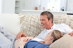 Couple lying down on the couch Stock Image