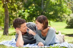 Couple lying down in the park Stock Photos