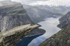 Couple lying down on trolltunga troll`s tongue rock , Norway royalty free stock photos