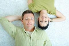 Couple lying on floor stock photos
