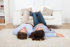Couple lying on floor with feet up on sofa Stock Photos