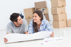 Couple lying on the floor and holding house plans. In their new house royalty free stock photography