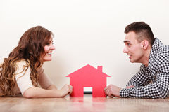 Couple lying on the floor holding paper house Stock Photography