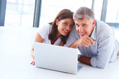 Couple lying on the floor with a laptop in front Royalty Free Stock Photos