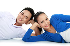 Couple lying on the floor looking at camera Stock Photos