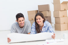 Couple lying on the floor and looking at house plans. In their new house royalty free stock photos