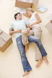 Couple lying on floor by open boxes in new home Royalty Free Stock Image