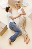 Couple lying on floor by open boxes in new home Stock Images