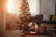 Couple lying on the living room floor next and exchanging Christmas presents. Couple lying on the floor and opens up glowing gift Royalty Free Stock Photography