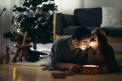 Couple lying on the living room floor next and exchanging Christmas presents. Couple lying on the floor and opens up glowing gift Stock Images