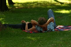 Couple lying on grass. Couple relaxing in park within the shadows of the trees stock images