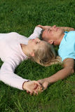 Couple Lying on Grass Stock Photos
