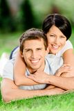 Couple lying on the grass embraces each other Royalty Free Stock Photos