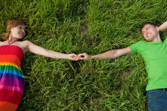 Couple lying on grass and enjoys Stock Photos
