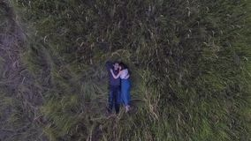 Couple lying in the grass in a field stock video