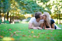 Couple lying on the grass and kissing Stock Images