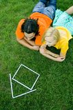 Couple lying on grass with model house Stock Photos