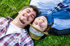 Couple lying on the grass in a park. Young men and young women smiling in park Stock Photos
