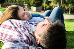 Couple lying on the grass in a park. Young men and young women smiling in park Stock Photo
