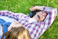 Couple lying on the grass in a park. Young men and young women smiling in park Royalty Free Stock Photos