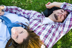 Couple lying on the grass in a park. Young men and young women smiling in park Stock Image