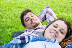 Couple lying on the grass in a park Stock Photography