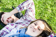 Couple lying on the grass in a park Stock Image