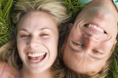 Couple lying in grass smiling Stock Image