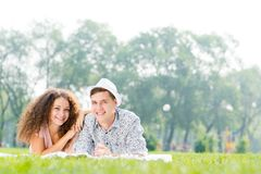 Couple lying on the grass in the summer park Royalty Free Stock Photos