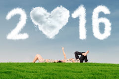 Couple lying on grass under numbers 2016 Stock Photo