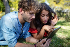 Couple lying on grass and using digital tablet Royalty Free Stock Photos