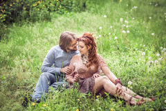 Couple lying on the green grass and blowing on the dandelion fie Stock Images