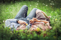 Couple lying on the green grass and blowing on the dandelion fie Stock Photography