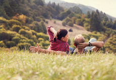 Couple lying in green grass on the forest hill Stock Photo