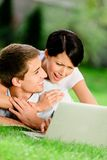 Couple lying on the green grass with silver laptop Royalty Free Stock Photography