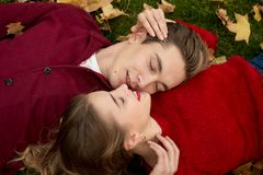 A couple is lying on green grass in yellow maple leaves, their faces are close to each other, a date, lovers, a married couple, an royalty free stock image