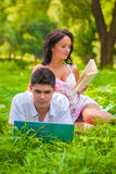 Couple lying with laptop and book at park Royalty Free Stock Image