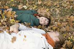 Couple Lying On Maple Leaves Royalty Free Stock Photography