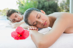 Couple lying on massage table at spa center Stock Photos