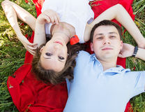 Couple lying on a meadow full of poppies Stock Photography