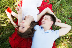 Couple lying on a meadow full of poppies Royalty Free Stock Photography