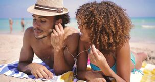 Couple lying with music on beach. Happy young ethnic couple lying together and listening to music with earphones on beach at the ocean stock video footage