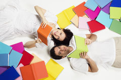 Couple Lying On Floor Reading And Looking Up. Royalty Free Stock Photos