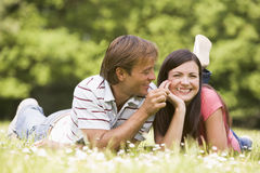 Couple lying outdoors with flower smiling Stock Images